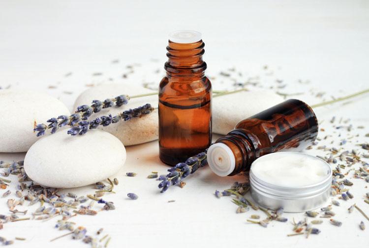 fläschchen mit lavendelöl, seife und cremetiegel auf einer weißen oberfläche mit lavendelblüten
