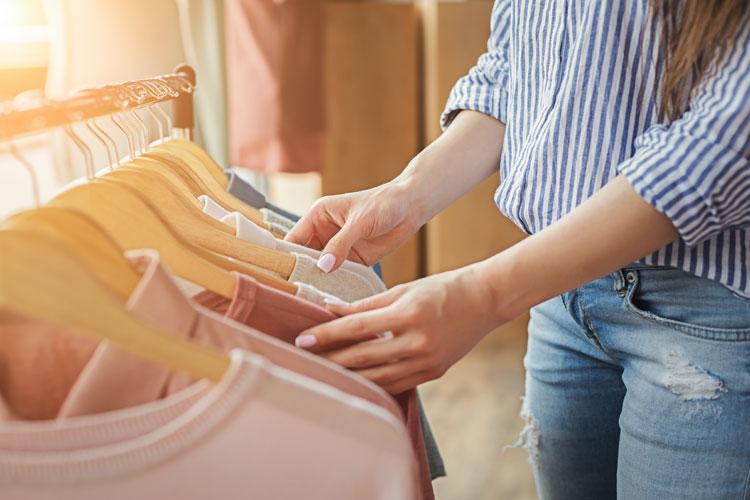 frau durchsucht kleidung an kleiderstange