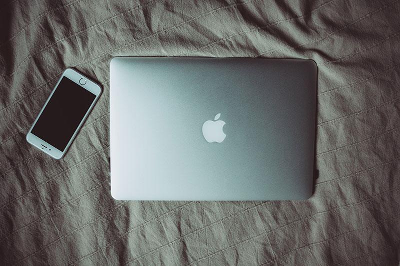laptop und smartphone auf bett liegend