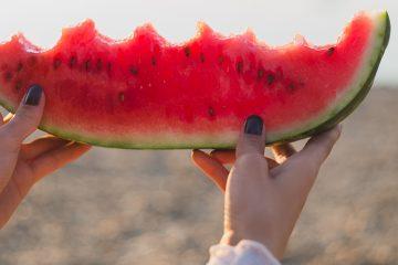 frau mit angebissener melone in den händen