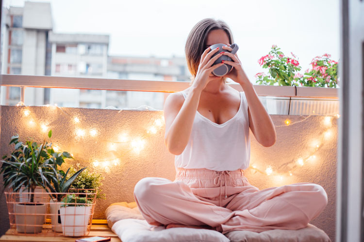 frau sitzt auf einem balkon mit lichterkette und trinkt aus einer tasse