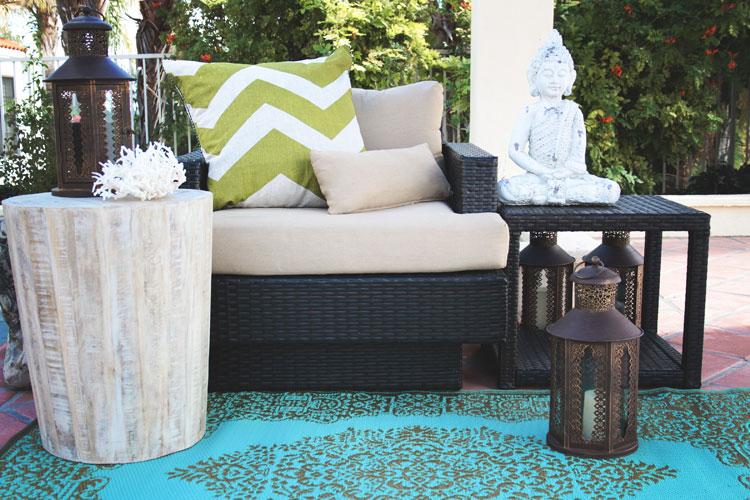 loungemöbel auf einer terrasse umgeben von laternen und buddhafiguren