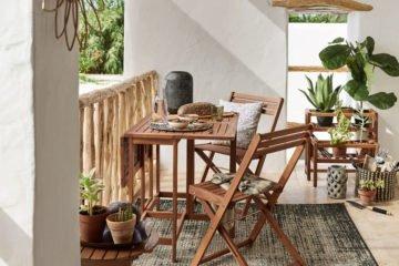 blick auf einen balkon mit holzmöbeln von depot und pflanzen