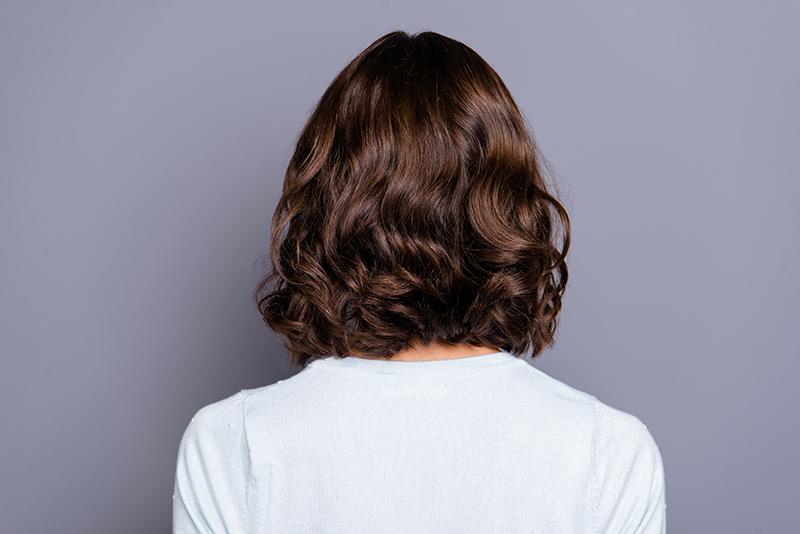 frau von hinten mit lockigen braunen haaren