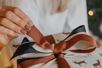 Frau packt Beauty-Weihnachtsgeschenk aus