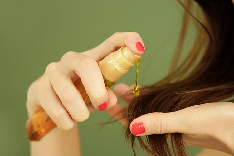 frau macht sich haaröl auf die haarspitzen