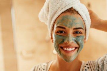 lachende frau mit handtuch auf dem kopf und grüner gesichtsmaske