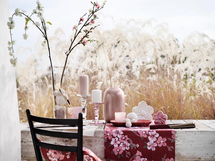 verschiedene deko objekte in rosa, weiß und pink auf einer fensterbank vor einem kornfeld arrangiert