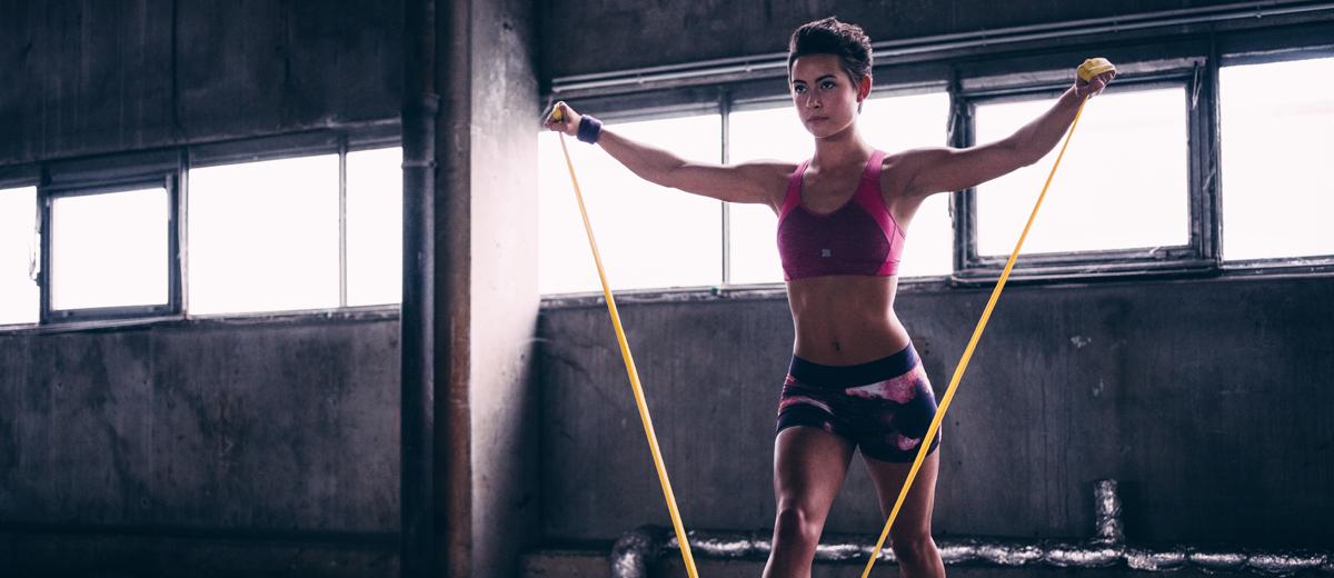 junge frau traniert mit einem gelben fitnessband im studio
