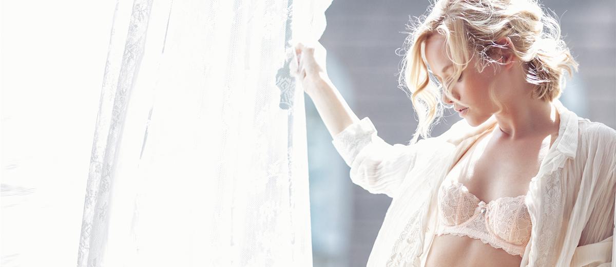 frau im tageslicht gekleidet in spitzenunterwäsche und bluse auf balkon mit vorhang in der hand