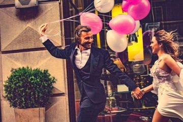 Lachendes Brautpaar mit Luftballons geht Hand in Hand die Straße entlang