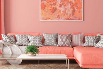 große couch mit hocker in der trendfarbe living coral vor einer wand in living coral mit einem wandbild im bilderrahmen