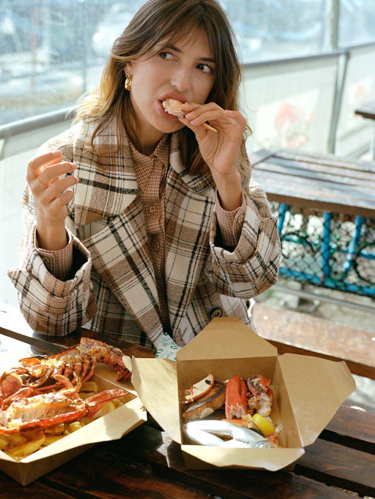 Jeanne Damas als Model für Mango sitzt an einem Tisch im Café und isst