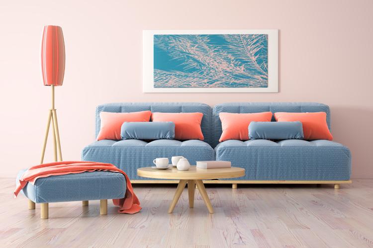 blaue couch im hellen wohnzimmer mit kissen, decke und stehlampe in der trendfarbe living coral