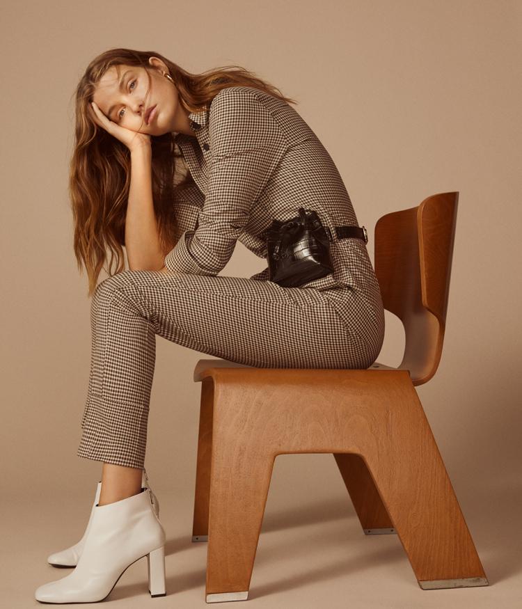 sitzendes model auf holzstuhl mit gürtasche von mango
