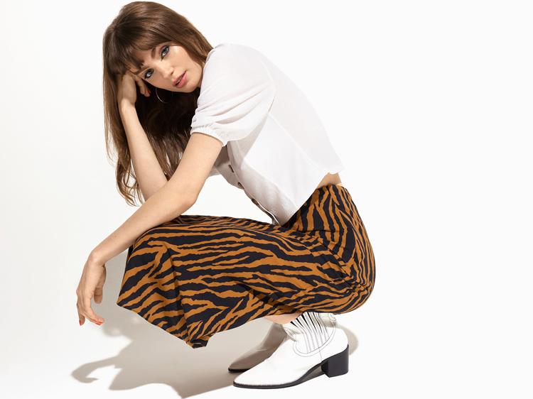 hockendes model in ein weißen t-shirt und einen rock im tiger print von der marke miss selfridge gekleidet