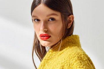 frau mit rotem lippenstift und gelber teddy-jacke
