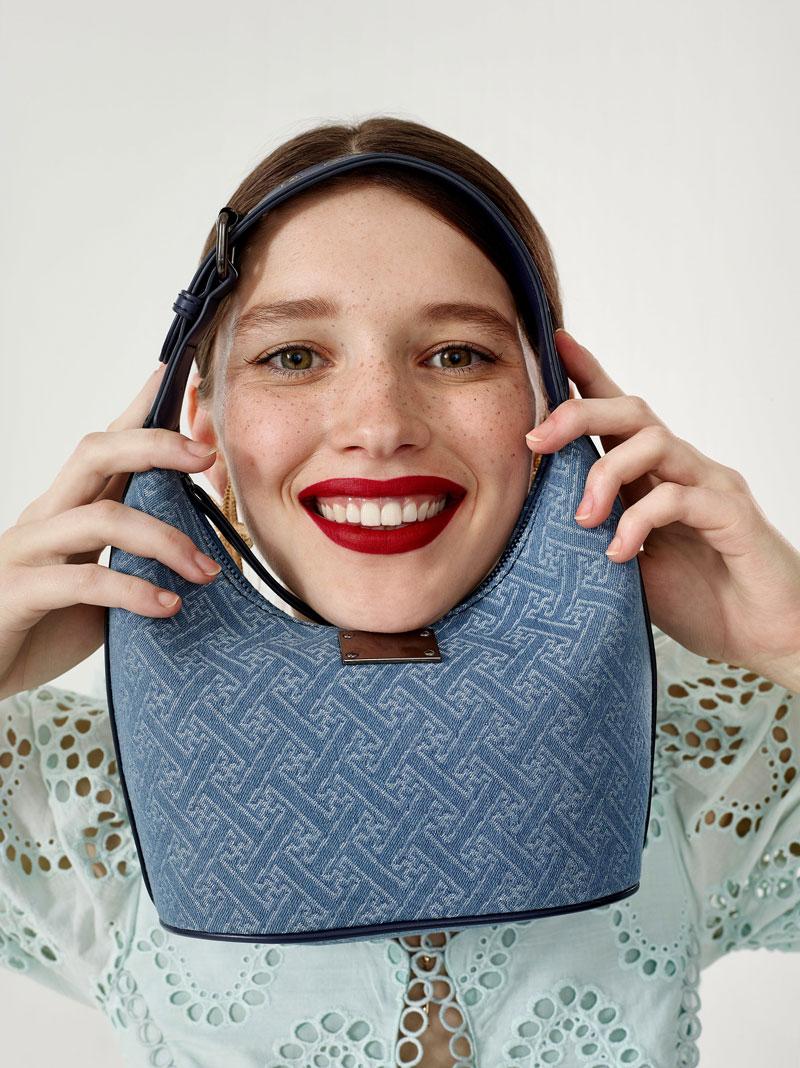 lachende frau mit blauer tasche