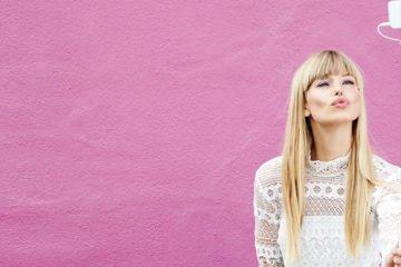 junge frau posiert vor pinkfarbener Wand mit selfie-stick