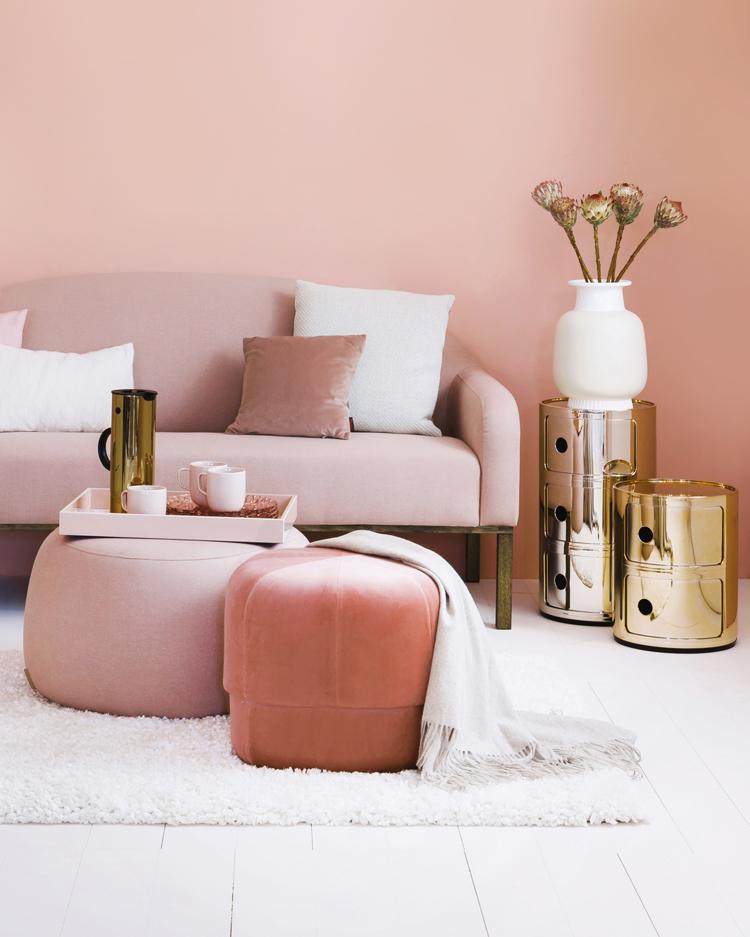 ausschnitt aus einem wohnzimmer mit sofa und hocker in living coral und rose. daneben beistelltische in gold