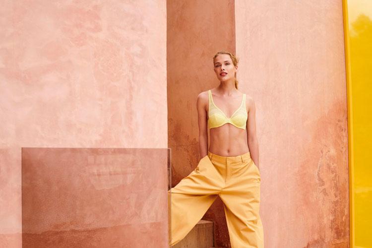 blondes dessous model trägt gelbe hose und gelben high apex-bh von marie jo l´aventure