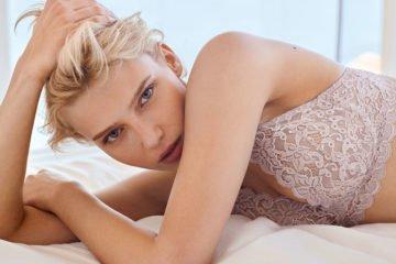 blondes dessous model liegt auf bett und trägt high apex-bh von hanro