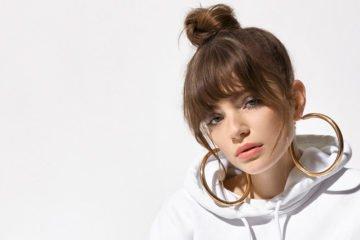 model trägt große goldene Ohrringe und die Haare zu einem lockeren hohen Dutt