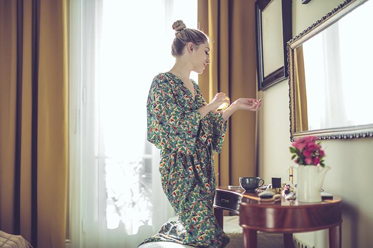 frau im bademantel sprüht sich parfum auf das handgelenk