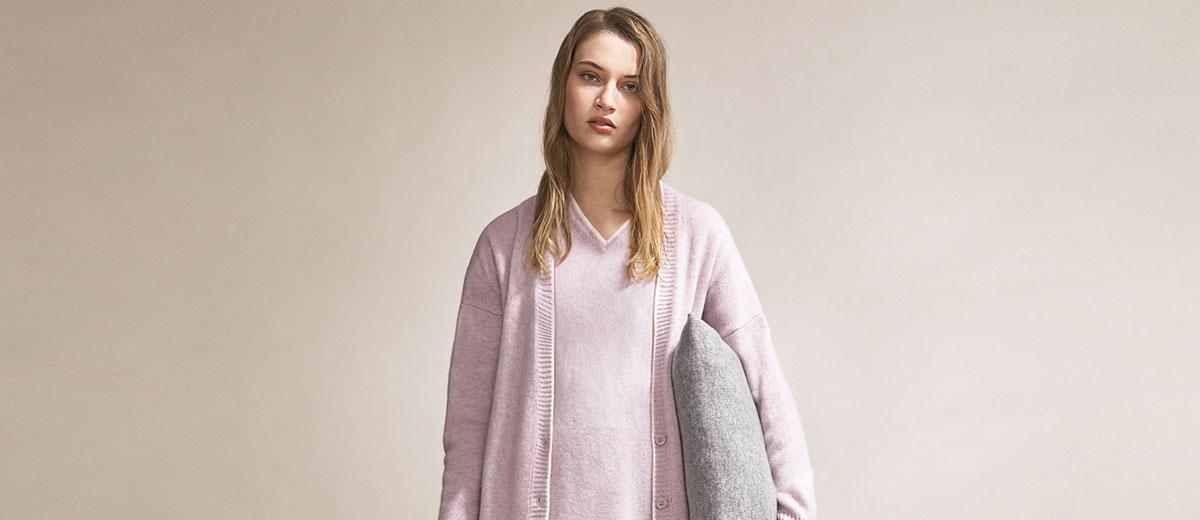 junges model von zara trägt gemütliche loungewear und kissen unter dem arm