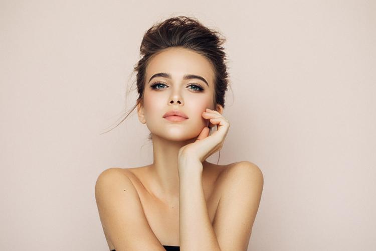 junge frau mit schöner haut und natürlichem make-up schaut in die kamera