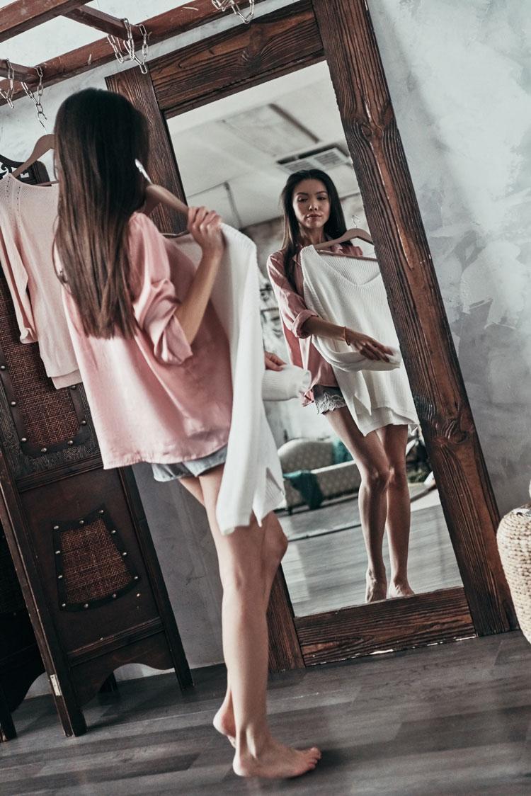 junge frau probiert vor dem spiegel kleidung an