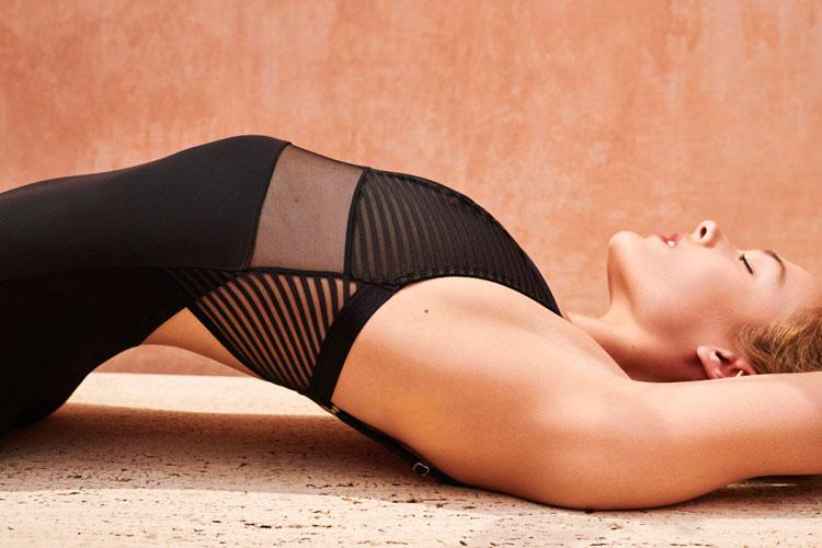 model in schwarzem body mit transparenten einsätzen der marke MarieJo L'Aventure räkelt sich auf dem boden