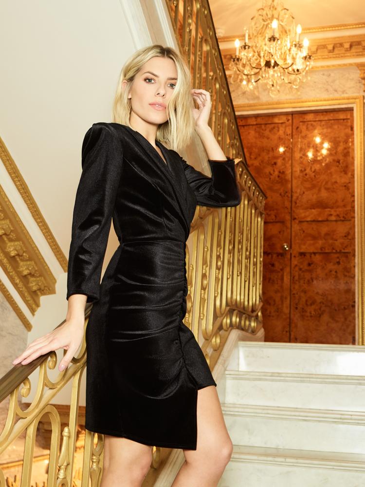 blonde frau in schwarzem kleid auf einer treppe