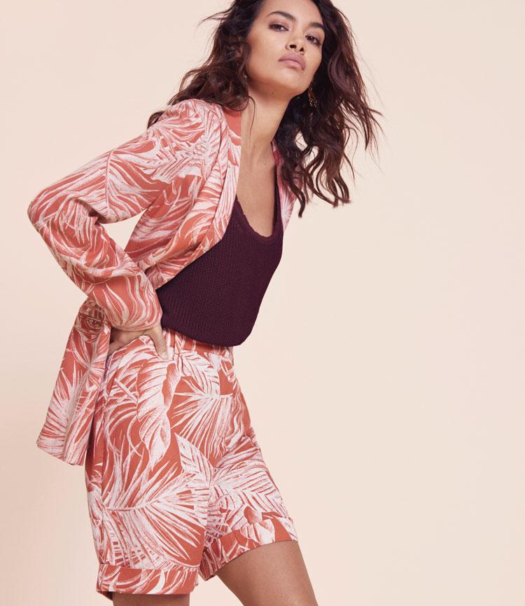 model trägt blazer und shorts aus leinen mit tropischem print in korallenrot von monsoon