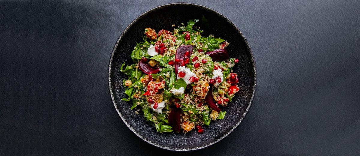 schale mit salat aus quinoa, rüben, spinat und granatapfelkernen auf einem dunklen untergrund