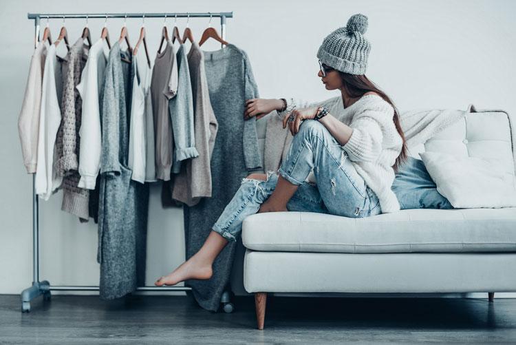 junge frau sitzt auf einer couch und betrachtet kleidung an kleiderstange