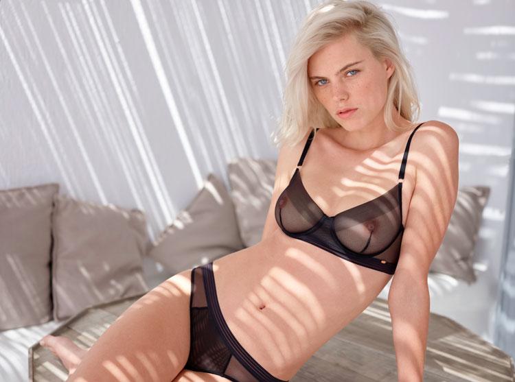 blondes model in schwarzen transparenten dessous der marke skiny sitzt auf einer bank