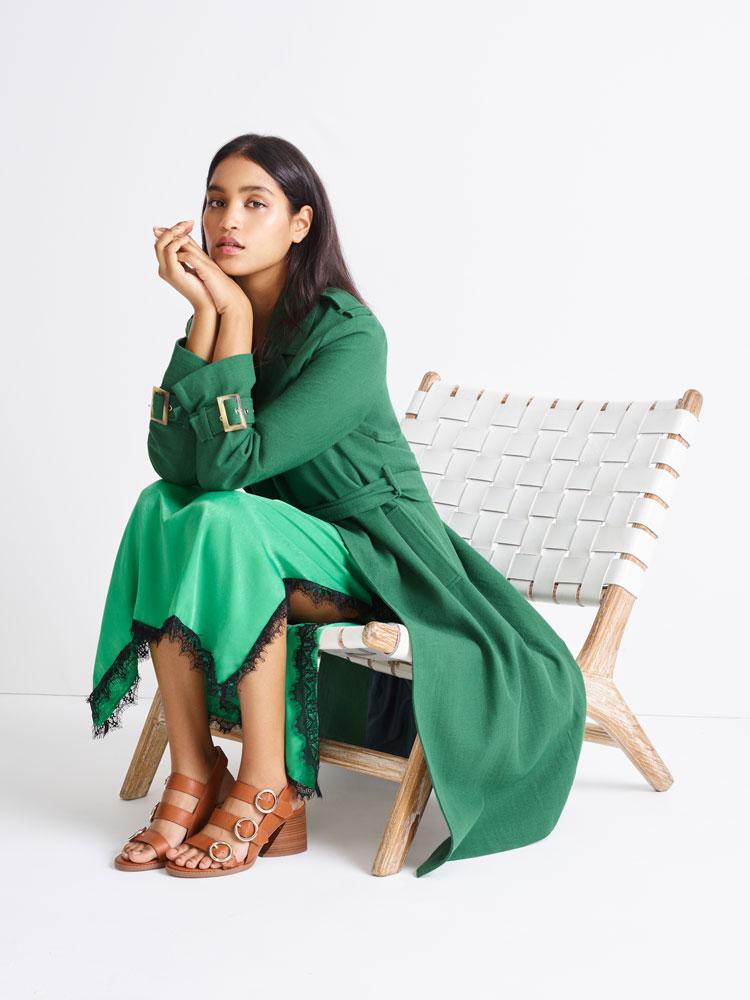 dunkelhäutiges model trägt grünen trenchcoat und sitzt auf einem stuhl