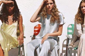 drei junge frauen nebeneinander sitzend in der sonne