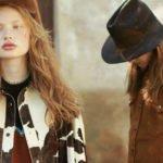 zwei junge frauen mit cowboy-hut und jacke in kuhfell-optik