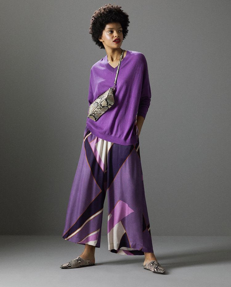 dunkelhäutiges model von zara in lila strickpullover und weiter seidenhose