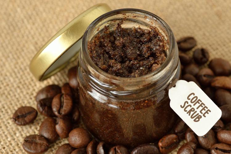 glas mit selbstgemachtem kaffeepeeling und kaffeebohnen auf einem tisch