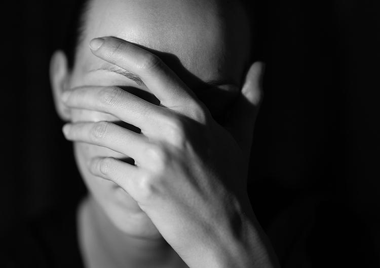 gestresste frau mit hand vor dem gesicht
