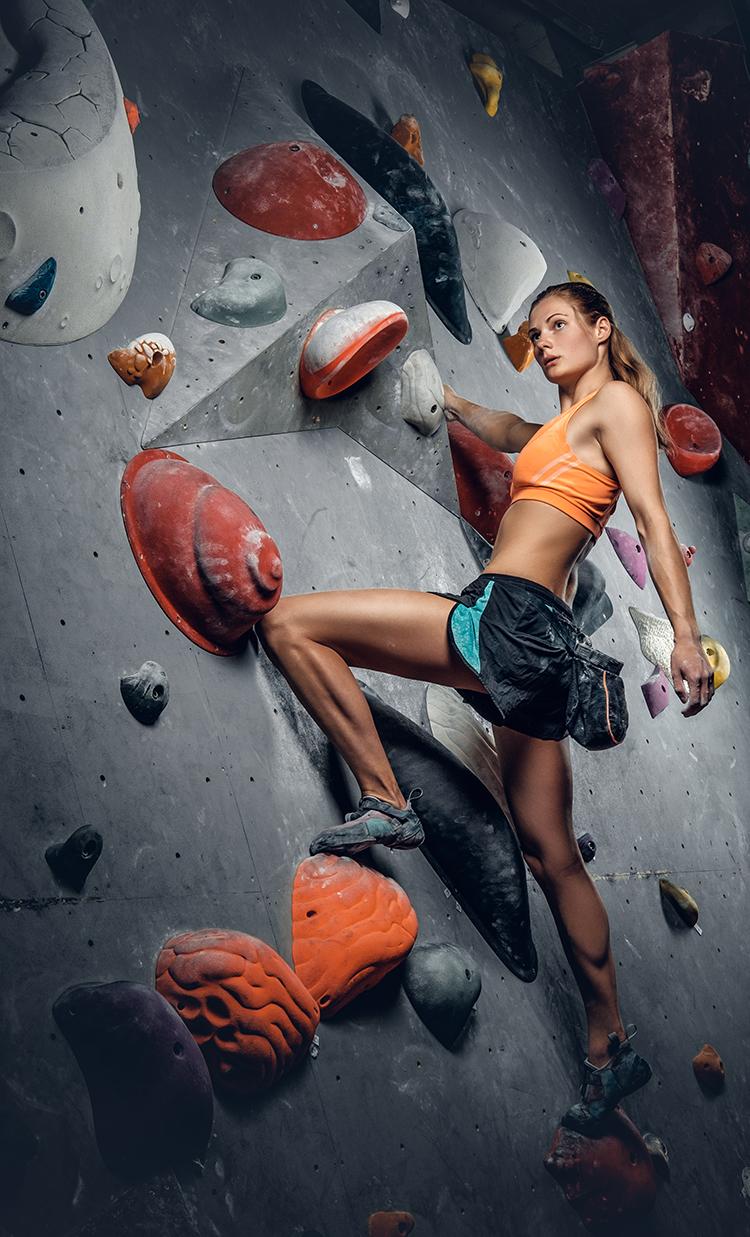 junge frau klettert an boulderwand