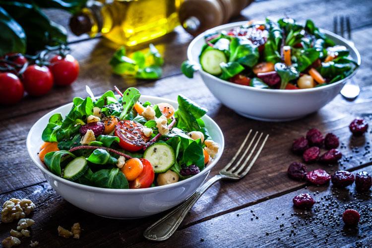 zwei schüsseln mit salat auf einem tisch
