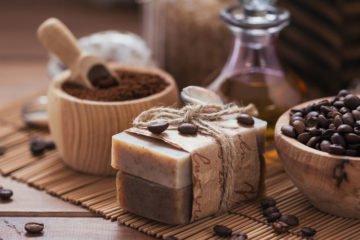 kaffeebohnen, gemahlener kaffee und seife aus kaffee auf einem holztisch