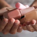 frau hält nagellack flaschen in den händen