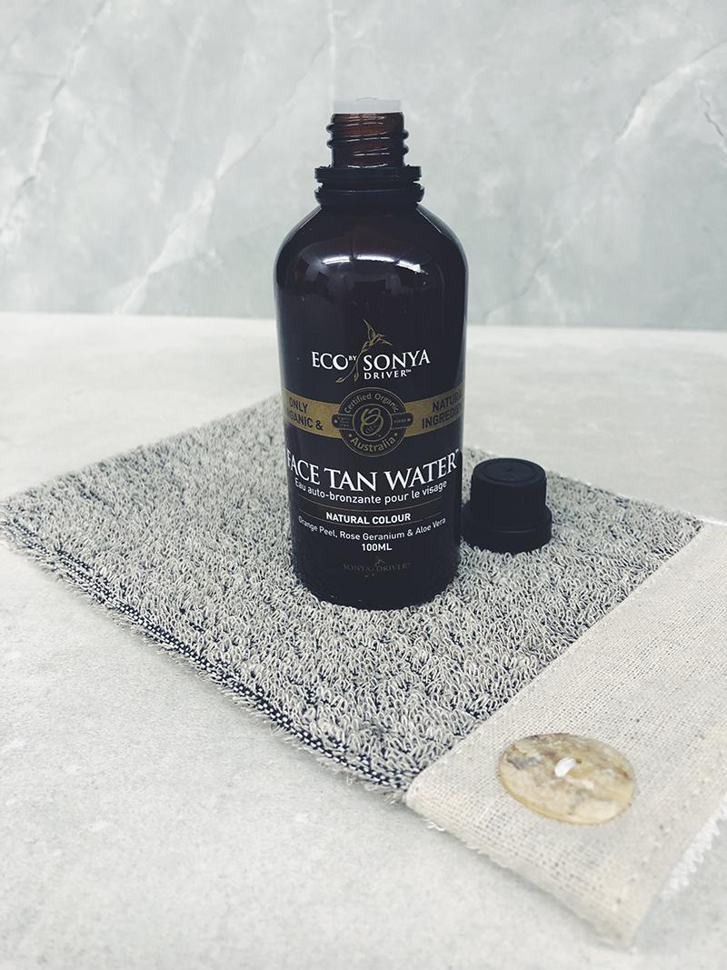 selbstbräuner-flasche vor grauem hintergrund
