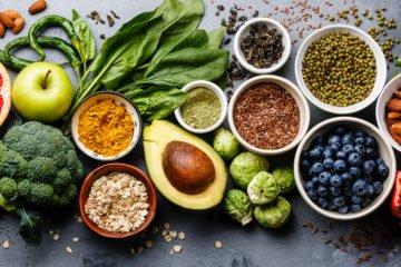 verschiedenes obst, gemüse, kräuter und samen angerichtet auf einem tisch