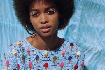 junge frau mit afro unnd hellblauem strickpullover mit eis-print